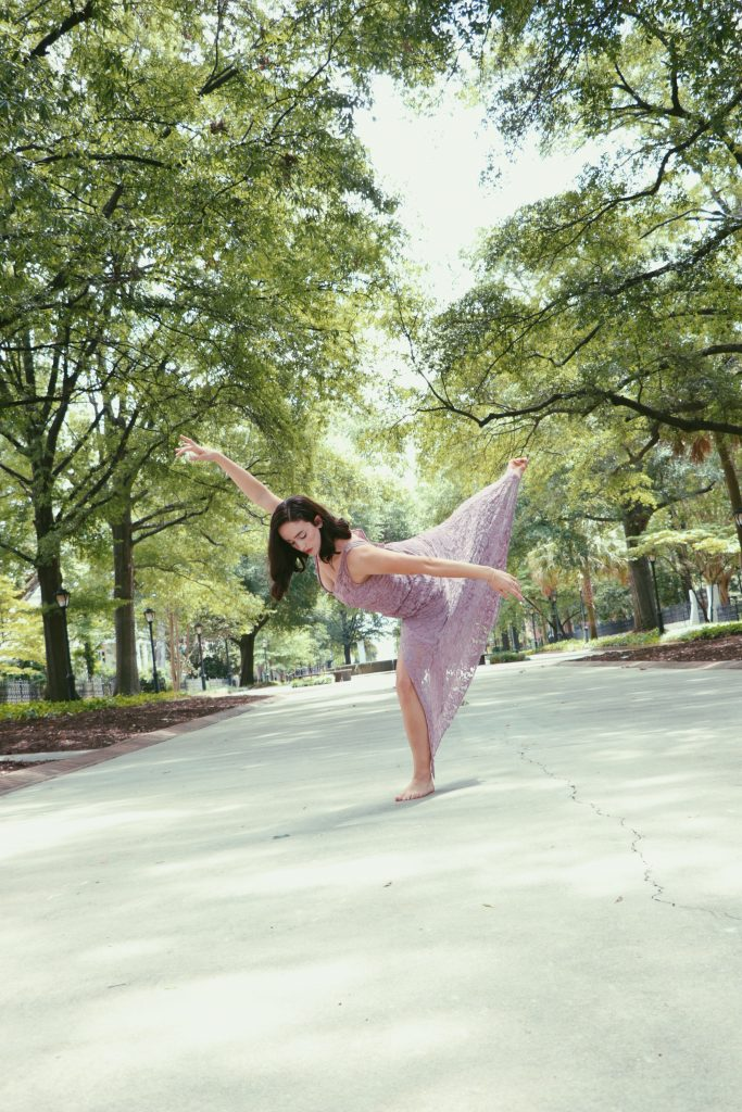 Kellie dancing on a tree-lined path